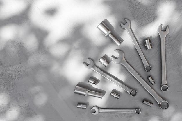 나무의 추상 그림자가 있는 회색 콘크리트 바닥에 있는 금속 도구는 배경을 남긴다
