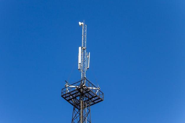 Металлическая башня с антеннами для мобильной связи на фоне голубого неба