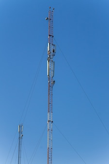 Metal tower with antennas for mobile cell phone communications against blue sky