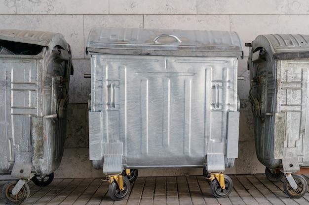 Metal trash can on wheels.