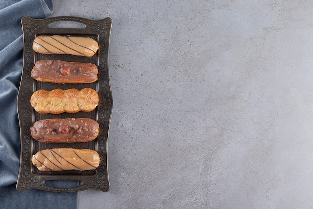 Metal tray of sweet tasty eclairs on stone surface
