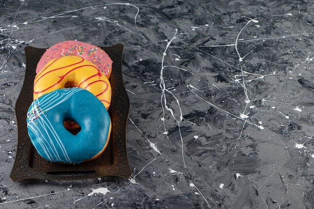 Metal tray of various delicious donuts with sprinkles on marble surface