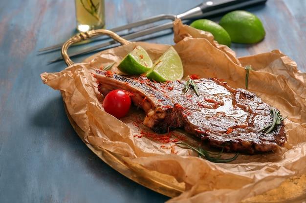 木製のテーブルに美味しいステーキのグリルが付いた金属製のトレイ