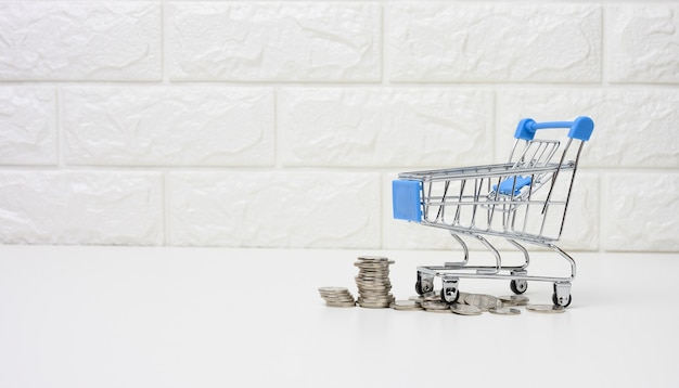 Metal trolley and small change on a white table. savings concept, discounts, low purchasing power