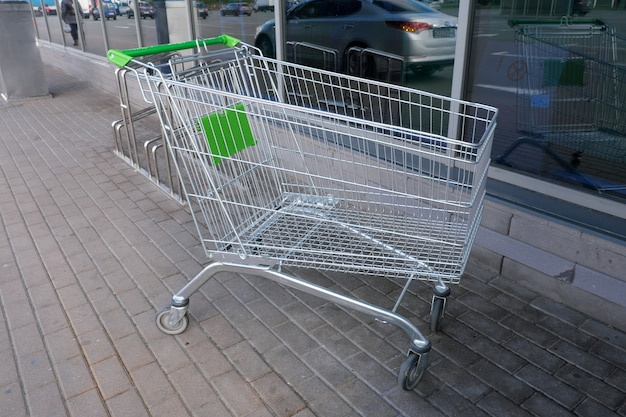 Metal trolley on wheels for purchases of goods in a supermarket near the entrance to the store, close-up