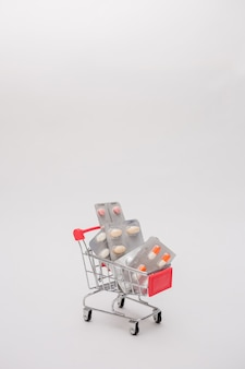 Metal вагонетка с таблетками на предпосылке изолированной белизной.