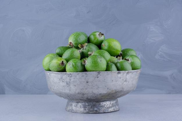 Vaso in metallo riempito con feijoas su fondo in marmo.