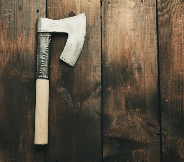 茶色の木製の背景、上面図、コピースペースに木製のハンドルを持つ金属ヴィンテージ斧