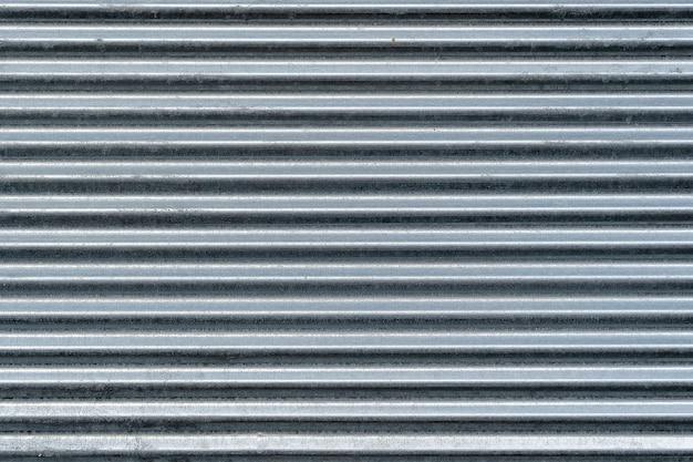 금속 벽 질감, 배경입니다. 건물 구조용 골이 있는 아연 도금 금속 시트. 표면에는 강성을 위해 수평으로 돌출된 리브가 있습니다. 울타리 건설을 위해 지붕을 덮는 데 사용됩니다.