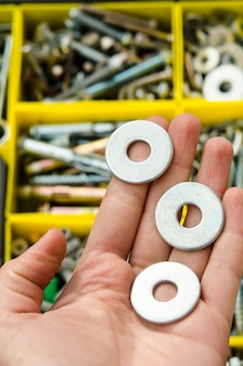 Metal washer in hand on the background of tools.