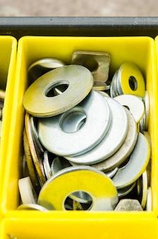 노란색 플라스틱 작은 상자에 금속 와셔.