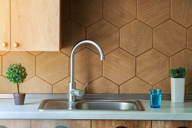 Metal water tap faucet with sink in the kitchen interior