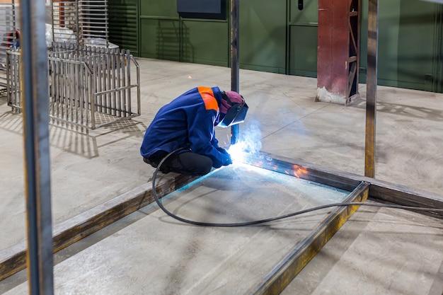 電気アーク溶接機を使用して工場で鋼を溶接する金属溶接製鉄所製造および手作業の技術労働概念による建設保守サービス