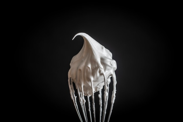 Metal whisk with whipped egg whites, isolated