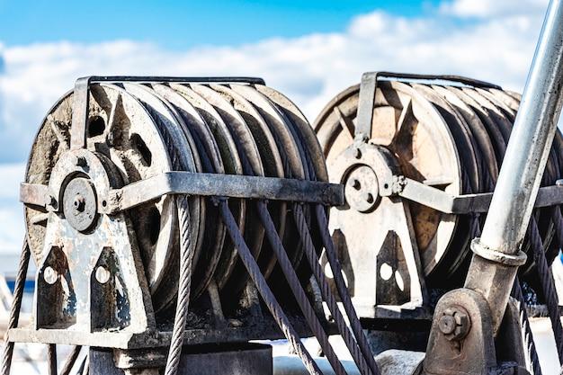 金属ウインチ。クレーンリールドラムまたはクレーンのウィンチロールのワイヤーロープスリングまたはケーブルスリングは、空を背景に重工業の吊り上げ機です。
