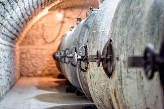 Металлические бочки для вина на фабричном подвальном туннеле