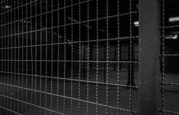 빈 창고의 금속 와이어 울타리. 사적인 영역의 어두운 배경. 보안을 위해 강철 울타리 벽.