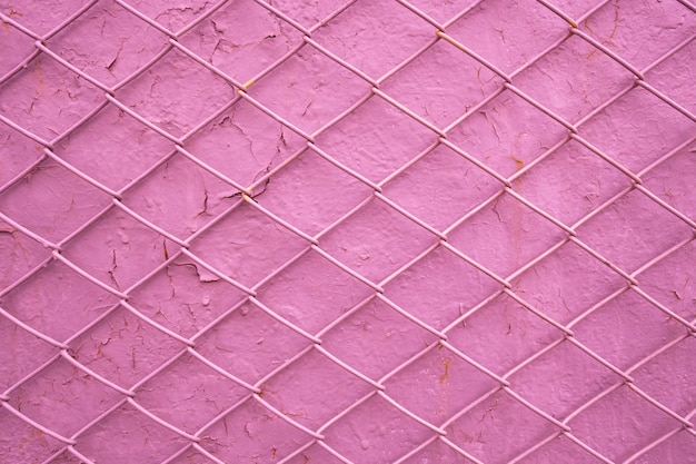 Metal wire grill on the background of an old pink wall with peeling paint. mesh texture as a concept of limitation of male freedom, dependence on women, lack of freedom, addiction