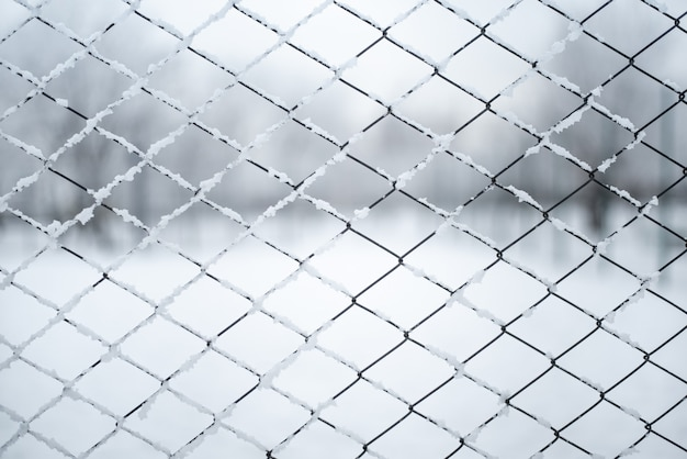 Metal wired fence under a snow - texture background.