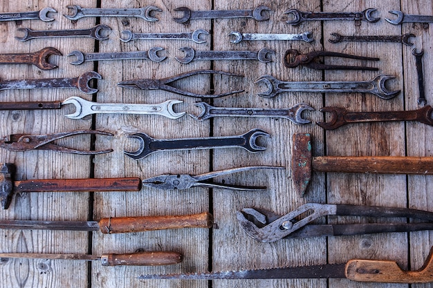 Metal wrench rusty tools lying on a black wooden table. hammer, chisel, hacksaw, metal wrench. dirty set of hand tools on a wooden panel with a tools