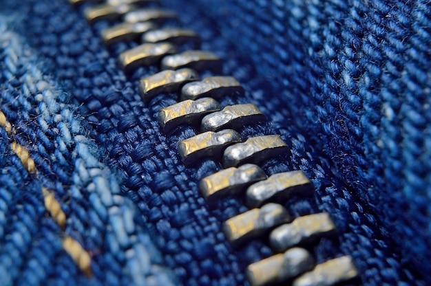 Metal zipper on blue jeans. macro