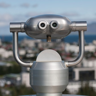 Металлический бинокулярный зритель над горизонтом города