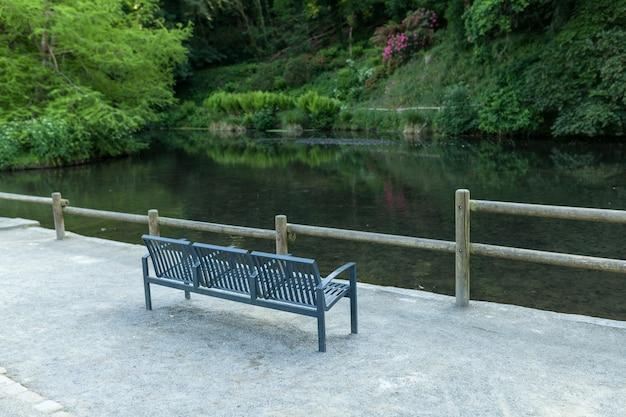 Metall bench on the lake shore