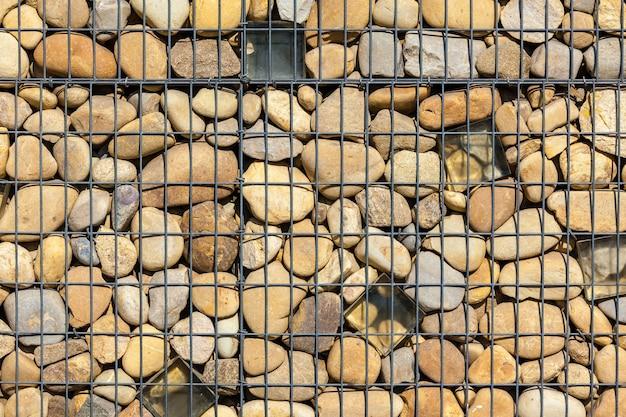 울타리로 자연석으로 채워진 금속 바구니 그물