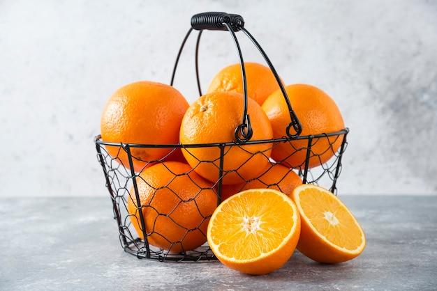 A metallic black basket full of juicy orange fruit on stone table .