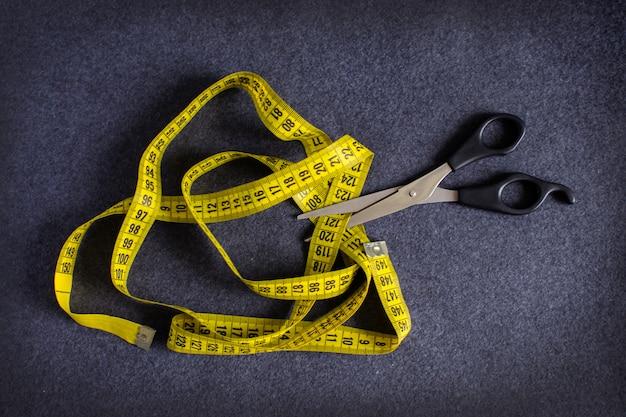 Metallic black scissors cutting yellow tape measure