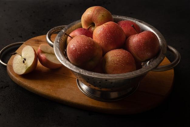 Металлическая миска, полная красных спелых яблок на натюрморт деревянной разделочной доски. ингредиенты для яблочного пирога. готовим дома