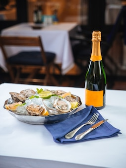 Metallic bowl with oysters and bottle of champagne