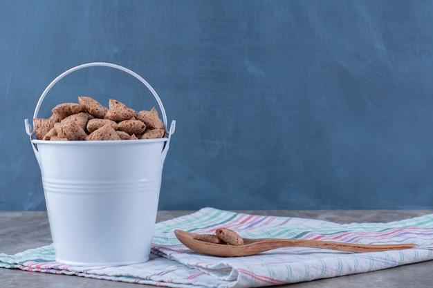 Un secchio metallico pieno di fiocchi di mais di cioccolato sano con un cucchiaio di legno.