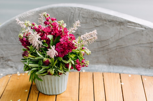 Metallic bucket with pink matthiola flowers on a wooden bench
