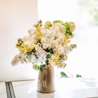 Metallic bucket with white lilac flowers by the window