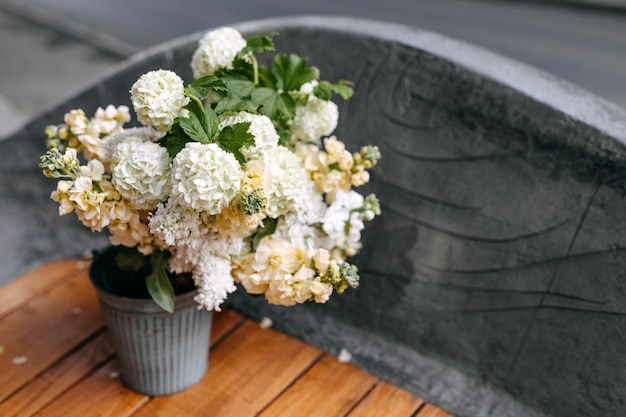 Metallic bucket with white lilac and matthiola flowers on a wooden bench