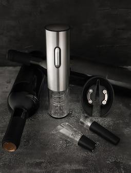 金属製の電子コードレスコルク栓抜き。近くには2本のワイン、エアレーターと真空コルクがあります。暗い背景。