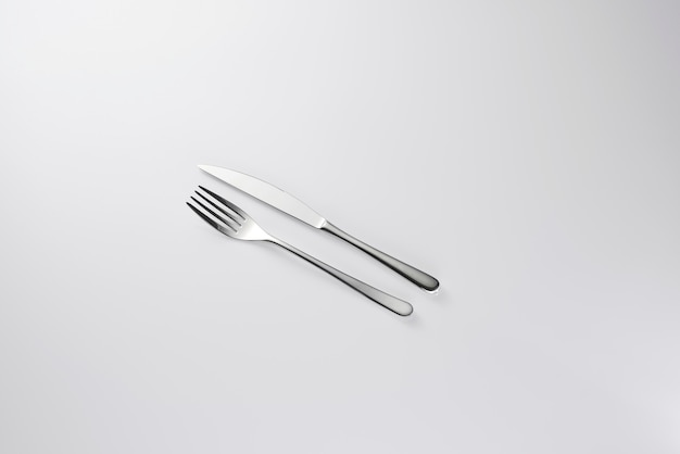 Metallic fork and knife on white