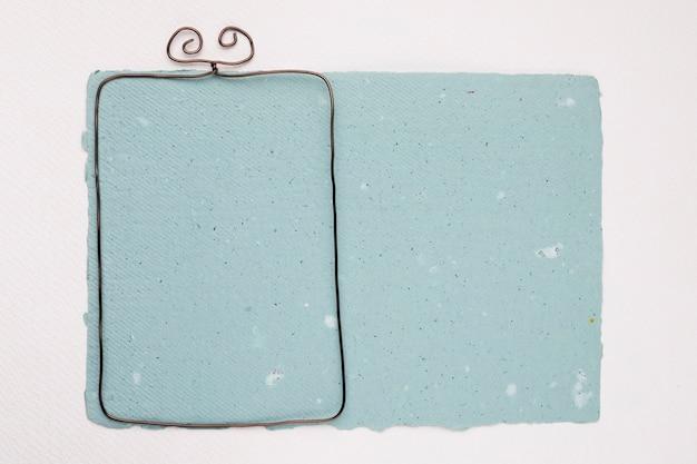 白い背景の青いテクスチャ紙の上の金属フレーム