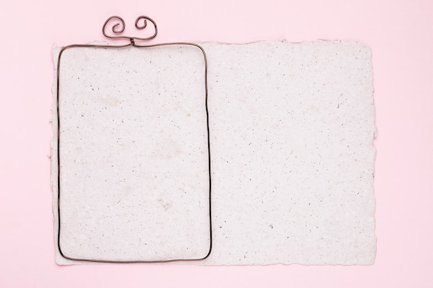 ピンクの背景の上の白いテクスチャ紙の上の金属フレーム