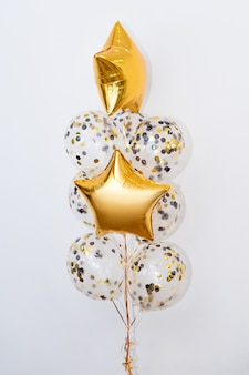 Metallic gold helium balloons of different shapes on white background. holidays and birthday party decoration concept