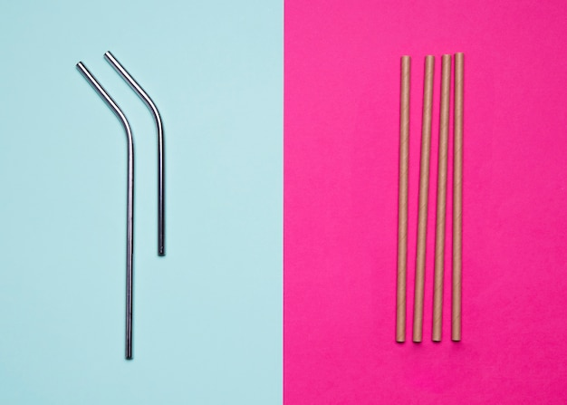 Metallic and paper straws on bicolored background