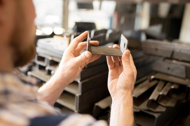 Металлическая запчасть для промышленного оборудования в руках ремонтника или техника по обслуживанию во время работы