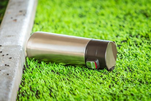 Металлическая бутылка с водой спорта на зеленом поле спорта.
