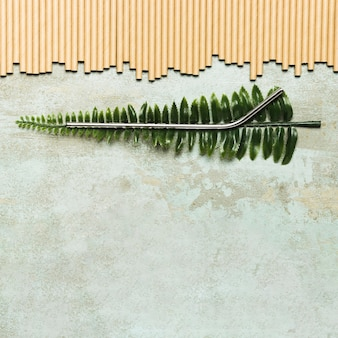 Metallic straw on fake leaf with copy space