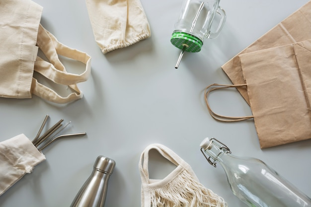 Metallic straws, cotton bag, glass and metal bottle on grey.