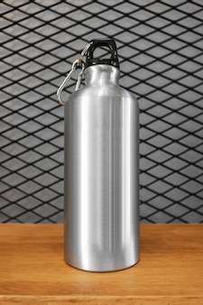 Metallic water bottle and carabiner on wood shelf background.