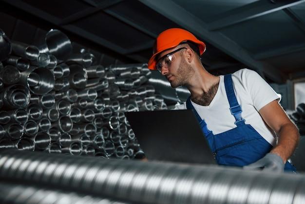 Металлургический завод. мужчина в военной форме работает на производстве. современные промышленные технологии.