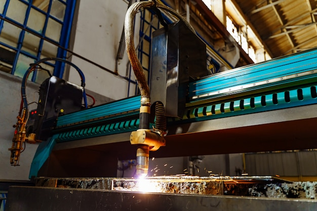 Metallurgical laser machine works to cutting metal indoor in the factory.