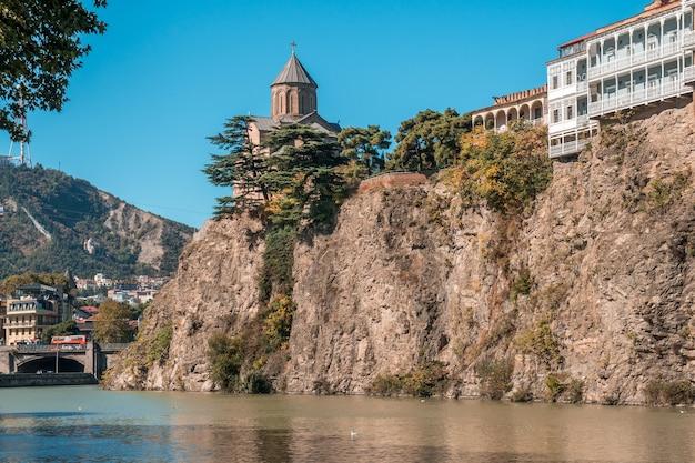 クラ川の上の崖の端にあるメテヒ教会と家々。ジョージア州の歴史的な市内中心部、トビリシ